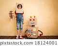 Happy child playing with toy robot 18124001