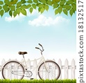 Bicycle in front of a white fence with leaves.  18132517