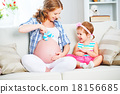happy family pregnant mother and child daughter preparing clothi 18156685