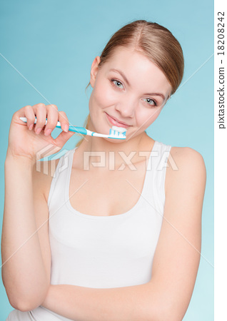 Stock Photo: woman holds toothbrush with toothpaste cleaning teeth