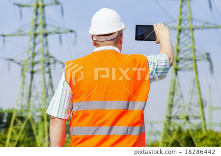Electrical engineer filmed with tablet PC near hig 18286442