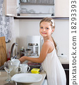 female child cleaning dishware at home 18293393