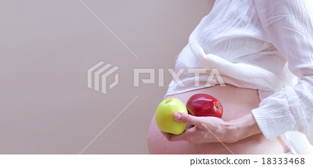 Stock Photo: A pregnant woman with two apples in her palm