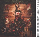 Woman in christmas tree dress in wooden interior with gift box 18344213