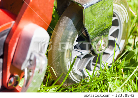 Closeup photo of red kick scooter wheel on grass 18358942