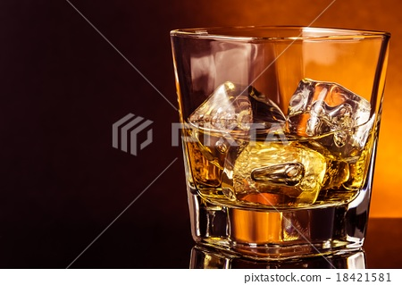 glass of whiskey on black table with reflection, warm atmosphere 18421581