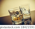 two glasses of whiskey on table with reflection, warm atmosphere 18421591