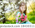 Adorable little girl in blooming cherry garden 18430311