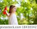 Adorable little girl holding a paper plane 18430342