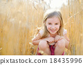 Adorable girl walking happily in wheat field 18435996