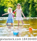 Two sisters playing with paper boats by a river 18436489