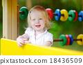 Toddler girl having fun at a playground 18436509