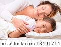 Delighted mother and daughter sleeping   18491714