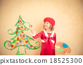 Child painting Christmas decorations 18525300