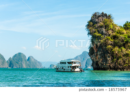 Boat docking in front of the big limestone rock 18573967