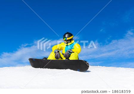 snowboarder sitting on snow mountain slope 18618359