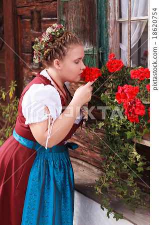 Young, Bavarian, chubby girl in dirndl smelling a  18620754