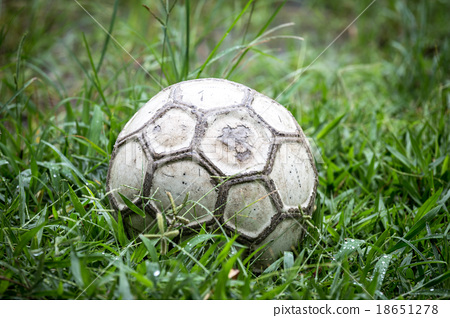 Old soccer ball in the grass on a rainy day. 18651278