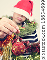 young man covered with christmas ornaments 18654699