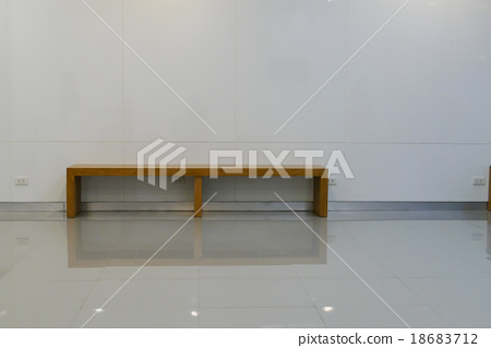 wooden seat beside th e white wall 18683712
