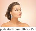 woman wearing shiny diamond earrings 18725353