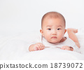 Asian baby lying on stomach. looking 18739072