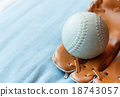 baseball in a glove on blue bed 18743057