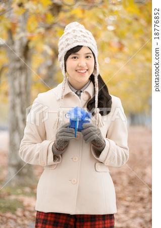 단풍 공원의 가로수 길에 서있는 코트를 입은 10 대 여성 18776852