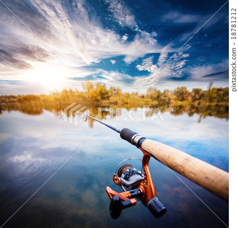 Fishing rod near beautiful pond with cloudly sky stock for Stocked fishing ponds near me