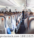 Interior of airplane with passengers on seats. 18811025