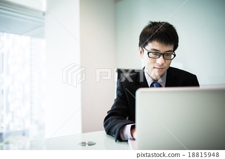 Stock Photo: Young handsome man using laptop in his office
