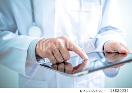 Stock Photo: Doctor working on a digital tablet