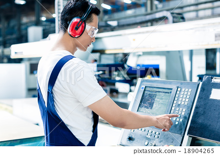 Stock Photo: Worker entering data in CNC machine at factory