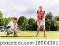 Senior woman and golf pro practicing their sport 18904301