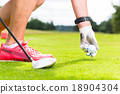 woman putting golf ball on tee, close shot 18904304