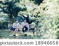 คู่หนึ่งนั่งอยู่บนม้านั่ง 18946658
