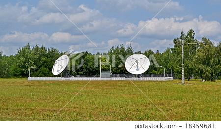 satellite antennas, green trees, blue sky 18959681