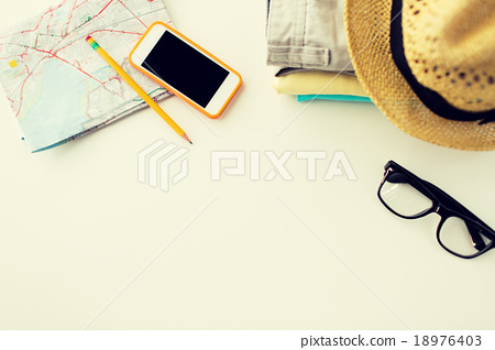 Stock Photo: close up of summer clothes and travel map on table