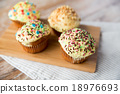 close up of glazed cupcakes or muffins on table 18976693