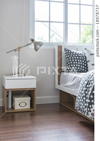 Stock Photo: modern lamp on bedside table with wooden bed