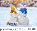 girl playing with a snowman 19010381