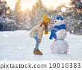 girl playing with a snowman 19010383