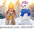 girl playing with a snowman 19010387