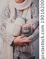 Woman with basket of balls woolen yarn 19016200