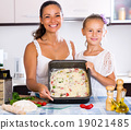 Mother and daughter making pizza 19021485