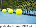 tennis ball on a tennis court with net 19045413