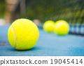tennis ball on a tennis court with net 19045414