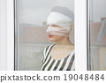 woman in bandages looking out of a window 19048484