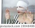woman in bandages looking out of a window 19048486