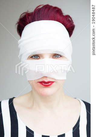 Stock Photo: portrait of woman with bandages wrapped around her head